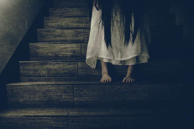 階段に座る不気味な女性