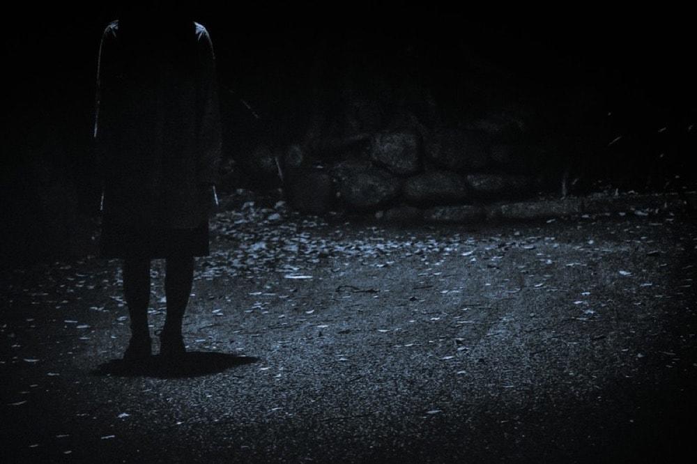 暗闇に佇む女性の霊