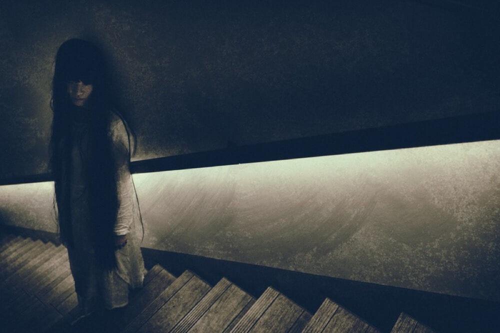 階段で佇む女性の霊