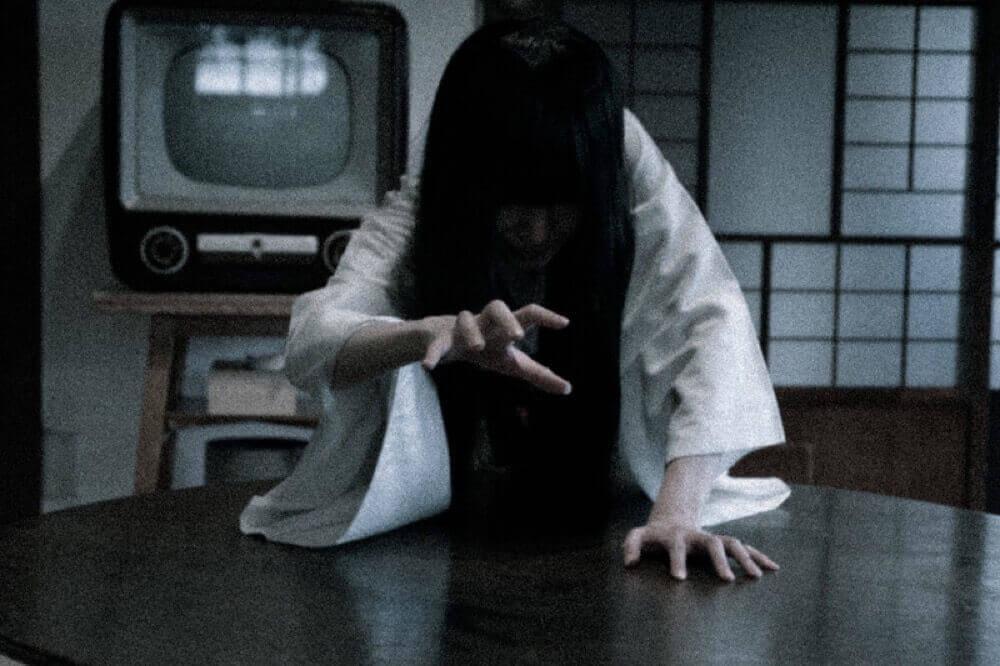 テレビの前で手を伸ばす女性の霊
