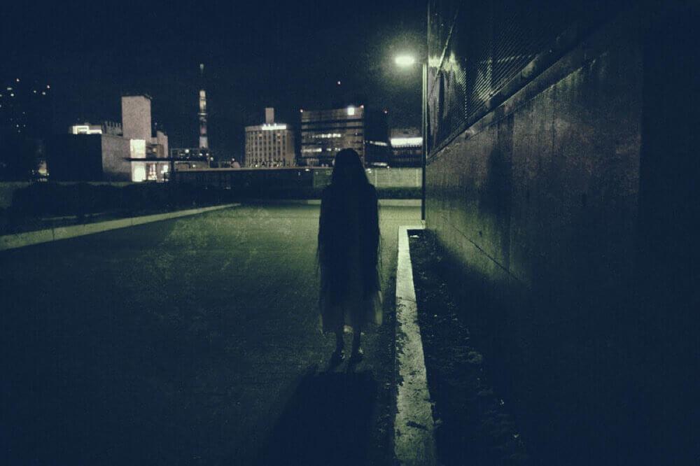 暗闇に佇む怪しげな女性