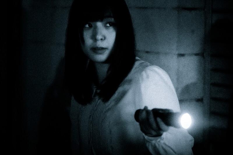 暗闇の中ライトを照らす女性